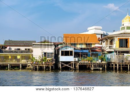Old Chao Phraya River Thai traditional houses village riverfront in Bangkok Thailand.