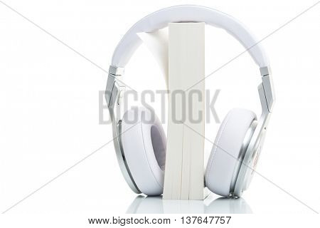 Audiobook concept - listen to your books in HD quality; hi-end hifi headphones over multiple books on white