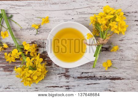 Rapeseed oil and flowers on wooden background top view.