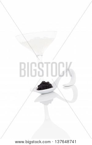 Delicious black caviar on spoon with vokda with ice isolated on white background. Exquisite luxurious gourmet eating.