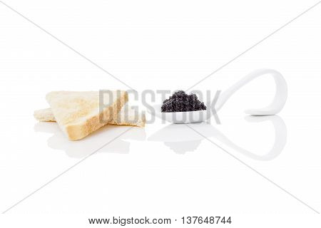 Delicious black caviar on toast isolated on white background. Exquisite luxurious gourmet eating.