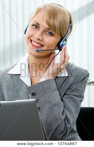 Portrait of beautiful smiling blond businesswoman in gray suit touching headset on her head in front of opened laptop