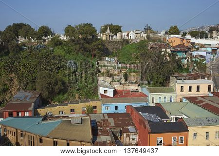 VALPARAISO, CHILE - JULY 5, 2016: Colourfully decorated houses crowd the hillsides below a historic cemetery of the historic port city of Valparaiso in Chile.