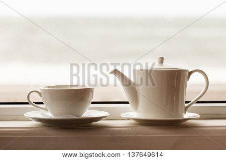 white teacup and teapot on the windowsill. Soft focus