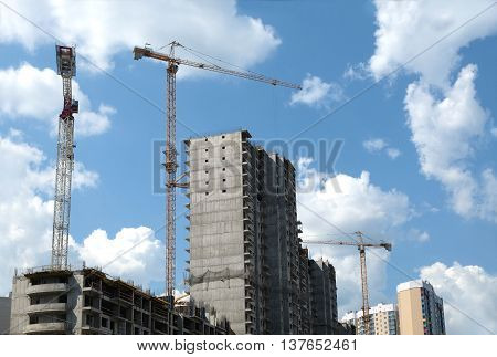 New high-rise modern apartment building construction in process ob bright sunny day front view top section