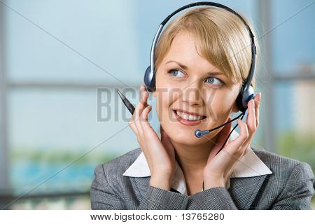 Portrait of beautiful smiling blond businesswoman in gray suit holding a pen in her hand and touching headset