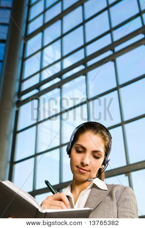 Portrait of beautiful brunette woman in gray suit with headset on her head writing details in the notebook and skyscraper with blue glassy walls on the background