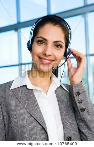 Portrait of beautiful smiling brunette woman in gray suit touching headset on her head and skyscraper with brunette glassy walls on the background