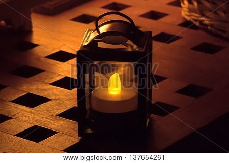 A close up shot of an old-fashioned electric lamp on a table in the dark