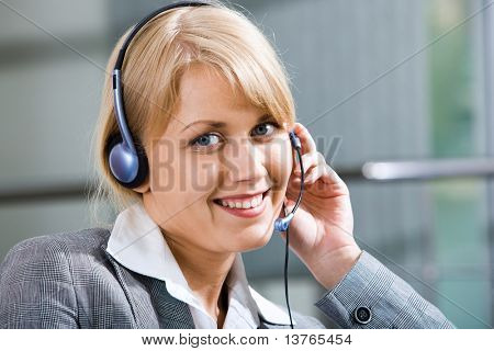 Portrait of beautiful smiling blond woman in gray suit touching headset on her head
