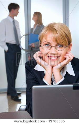 Portrait of cute smiling blond woman with eyeglasses in black suit touching her head working on laptop and two young businesspeople on the background