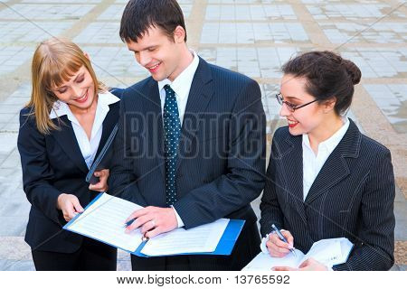 Smiling young women showing documents to their boss and a businessman attentively reading them outside