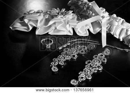 Close up of wedding garter and bridal jewelry and engagement ring