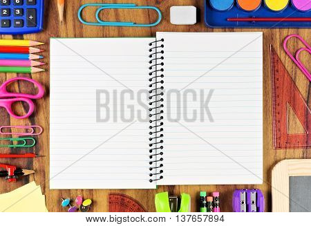 Opened Blank Lined School Notebook With Frame Of School Supplies Over A Wooden Desk Background