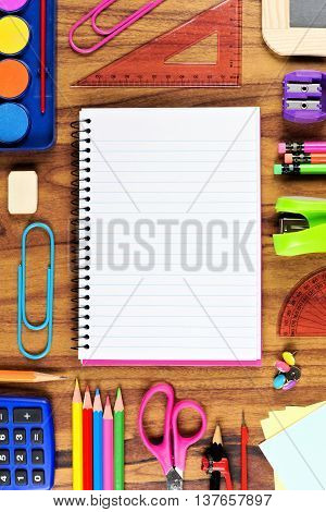Blank Opened Lined School Notebook With Frame Of School Supplies Over A Wooden Desk Background