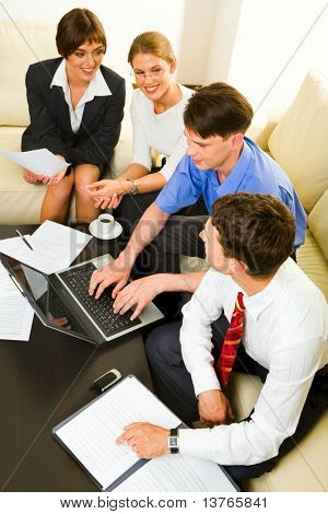 Portrait of two businesswomen and two businessmen sitting on the white sofas at the table with opened laptop and littered documents on it and discussing questions