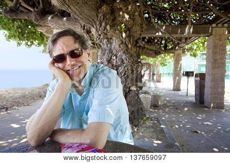 Handsome Caucasian man in forties relaxing under shaded tree canopy by ocean smiling head on hand