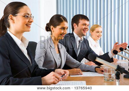 Vier erfolgreiche Jugendliche sitzen in einer Linie vor Monitoren spricht über Mikrofone sitzen