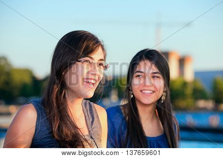 Two beautiful young women talking and smiling outdoors by lake