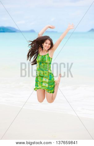 Beautiful biracial Asian Caucasian teen girl jumping in air on Hawaiian beach with tropical island scenery in background on sunny day