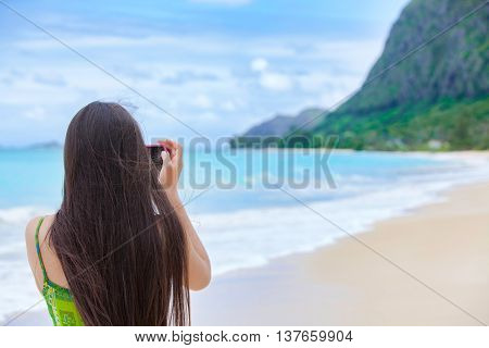 Back view of teen girl with long dark hair standing on tropical Hawaiian beach holding camera taking pictures or videos of scenery