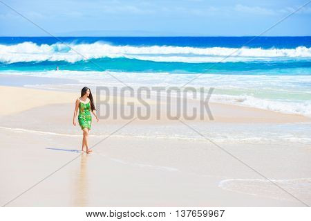 Beautiful biracial Asian Caucasian teen girl in green dress walking along empty secluded Hawaiian beach waves crashing onto shore on sunny day