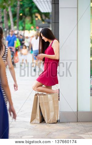 Beautiful biracial Asian Caucasian teen in red dress standing outside stores with shopping bags looking at her cellphone