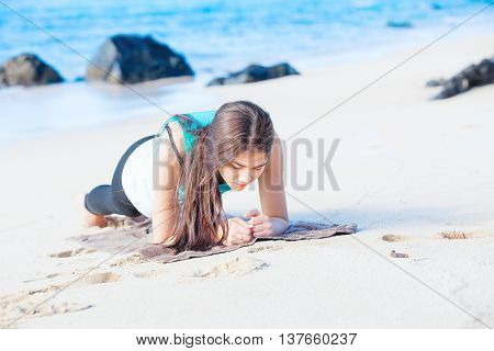 Beautiful biracial Asian Caucasian teen girl exercising on tropical beach planking