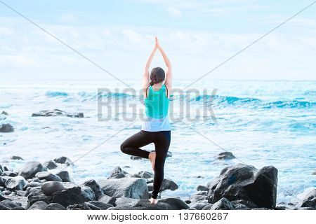 Slim fit biracial teen or young woman standing one legged on rocks by ocean in Hawaii exercising yoga with blue waves in background