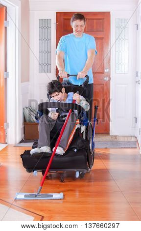 Father helping disabled nine year old biracial son in wheelchair clean the floor with a mop