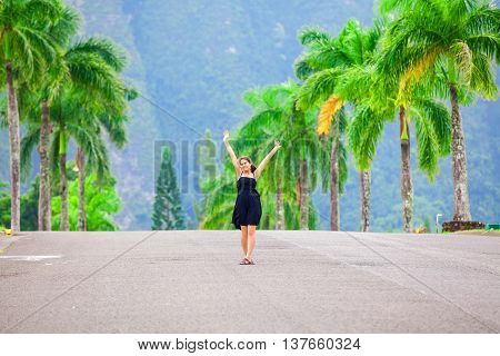 Beautiful biracial teen girl walking along palm tree lined road arms raised overhead in elegant black sundress in tropical setting Hawaii
