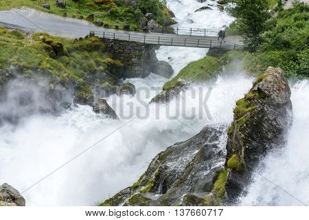 JOSTEDALSBREEN NATIONAL PARK, NORWAY - JUNE 29: Tourists go over the bridge on the way to the Briksdalsbreen glacier on June 29, 2016 in Jostedalsbreen National Park, Norway.