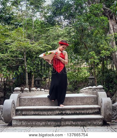 BAC Ninh, Vietnam, March 15, 2016 girl, wearing traditional dress. Passing a stone bridge, rural Bac Ninh, Vietnam