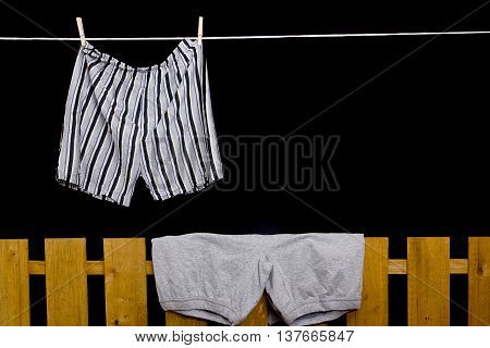 Men's and women's underwear hanging on the rope and on the fence