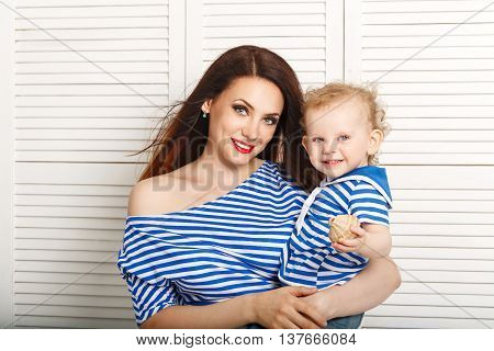 A young mother holds a baby daughter. Mother and daughter dressed in a striped t-shirt. Daughter holds a seashell. Close-up portrait