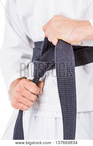 Close-up of fighter tightening karate belt on white background