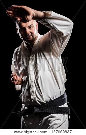 Portrait of fighter performing karate stance on black background