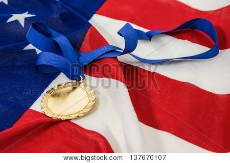 Close-up of olympic gold medals on american flag