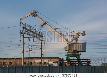Train wagons under industrial crane behind the fence