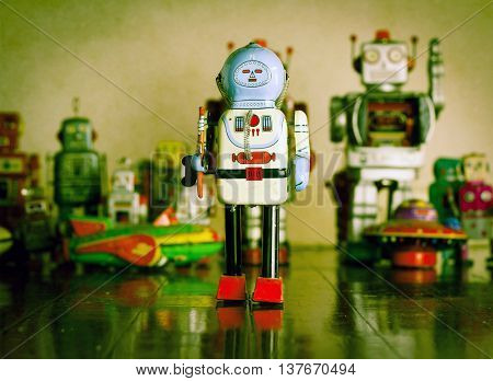 vintage robot toy stans alone on a wooden floor