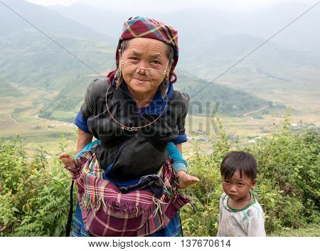 YEN BAI, VIETNAM, June 13, 2016 grandmother, mountain peoples, Yen Bai, carried him on his back, watched