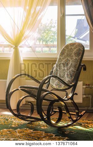 The rocking chair in the living room beside the window