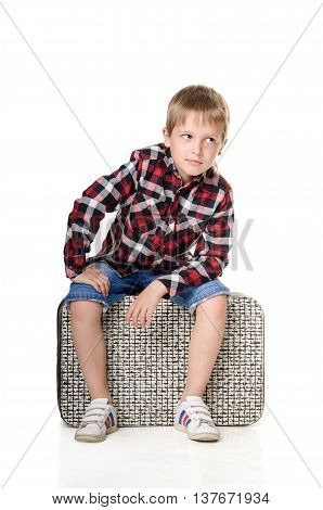 boy sitting on suitcase isolated on white background