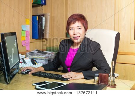 business woman asian manager senior age siting on desk look elegant