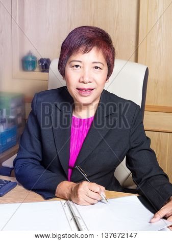 business woman asian manager senior age siting on desk sign document look elegant