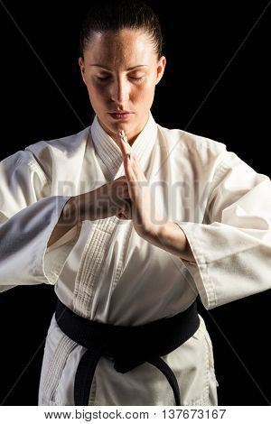 Portrait of female fighter performing hand salute on black background
