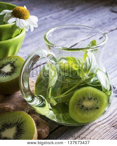 Glass jug with cold green tea with kiwi slices and oregano on wooden gray background. selective focus