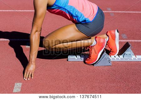 Female athlete ready to run on running track on a sunny day