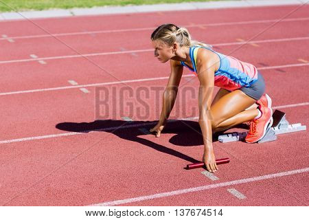 Female athlete ready to start the relay race on the running track