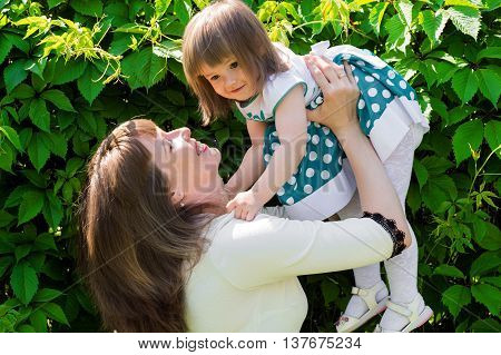 happy mother holding daughter outdoors on background